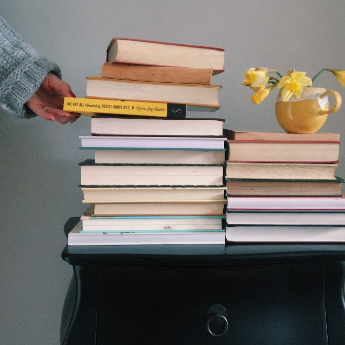 Image of a hand selecting a book from a large pile of books, it looks almost as if it might topple over.