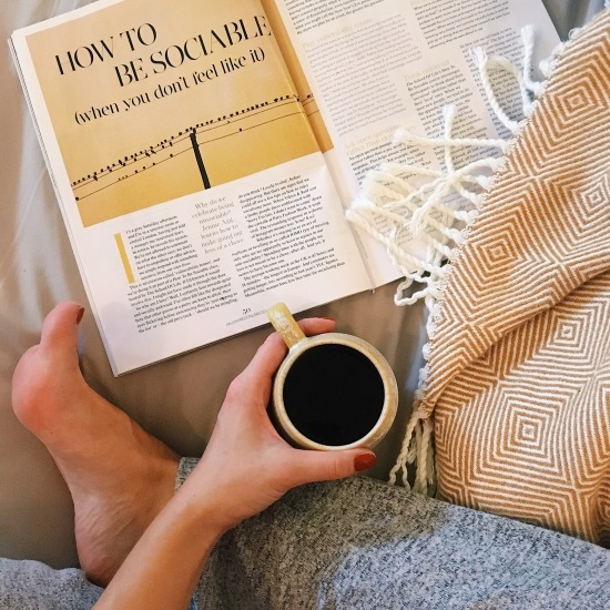 Aerial view of a woman sitting reading a magazine with a cup of coffee and a blanket - magazine headline reads 'how to be sociable when you don't feel like it'